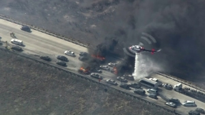 A helicopter drops water on vehicles burning on the 15 Freeway during the North Fire on July 17, 2015. (Credit: KTLA)