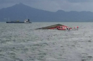 Rescuers search for survivors next to the capsized passenger ferry off Ormoc City, central Philippines on July 2, 2015. (Credit: STR/AFP/Getty Images)