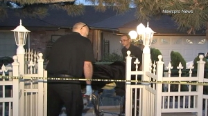 Officials remove a body from a home in San Bernardino after police received a domestic disturbance call. (Credit: Newspro News)