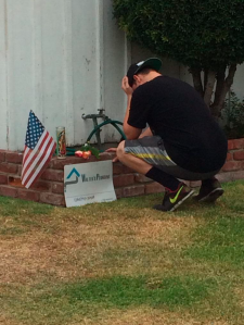 A mourner is seen outside a Norwalk home where Walter Vicente and his son Andrew Vicente were shot and killed on July 14, 2015. (Credit: KTLA)
