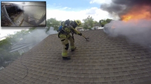 A screen shot from a body-cam video shows  a firefighter on the roof of a Victorville home that was engulfed in flames on Wednesday, July 29, 2015. (Credit: San Bernardino County Fire Department)