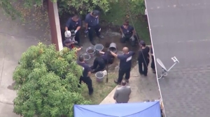 Sheriff's and coroner's investigators are seen digging in the backyard of a home near La Puente on Thursday, Aug. 6, 2015. (Credit: KTLA)
