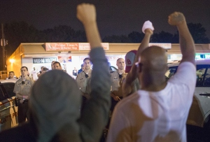 Demonstrators, marking the one-year anniversary of the shooting of Michael Brown, face off with police during a protest along West Florrisant Street on Aug. 9, 2015, in Ferguson, Missouri. (Credit: Scott Olson/Getty Images)