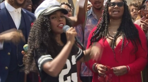 """Singer Janelle Monae leads a crowd in her protests song, """"Hell You Talmbout,"""" on Aug. 21, 2015, in Hollywood. (Credit: KTLA)"""