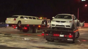 A limousine and car were hoisted onto tow trucks in the Newhall area after they were involved in a three-vehicle crash on Saturday, Aug. 1, 2015. (Credit: KTLA)