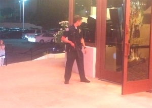 An officer is seen outside the Edwards Big Newport 6 movie theater on Aug. 8, 2015. (Credit: Katrina Wolfe)