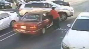 Surveillance video shows a store employee trying to pull a suspected robber out of the window of a getaway car. (Credit: Santa Ana Police Department)