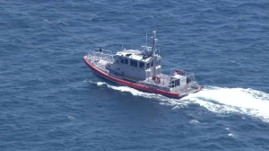 A U.S. Coast Guard response boat searches for a missing fisherman off Dana Point on Aug. 4, 2015. (Credit: KTLA)