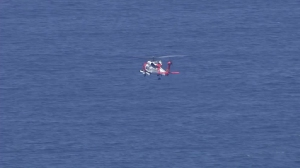 A U.S. Coast Guard helicopter searches for a missing fisherman off Dana Point on Aug. 4, 2015. (Credit: KTLA)