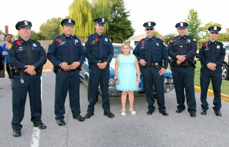 The daughter of Tim Warren, a fallen Memphis policeman, is seen with six officers who stepped in to escort her to a father-daughter dance. (Credit: Memphis Police Department)