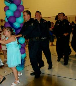 The daughter of Tim Warren, a fallen Memphis policeman, is seen with officers who stepped in to escort her to a father-daughter dance. (Credit: Memphis Police Department)
