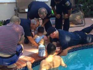Firefighters work to rescue a boy trapped in a pool skimmer at a home in Rancho Santa Margarita's Dove Canyon neighborhood. on Saturday, Sept. 5, 2015. (Credit: Orange County Fire Authority)