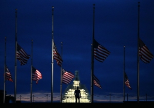 A man walks past a row of American flags that have been lowered to half staff on the Washington Monument grounds, near the US Capitol on Sept. 11, 2015, in Washington, D.C. (Credit: Mark Wilson/Getty Images)