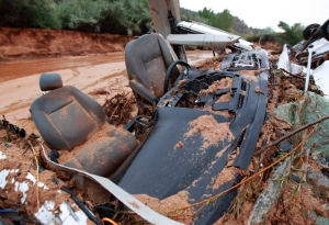 The twisted wreckage  of one of two vans that were washed away in a flash flood with women and children inside rest on the bank of Short Creek on Sept. 15, 2015, in Hildale, Utah. (Credit: George Frey/Getty Images)