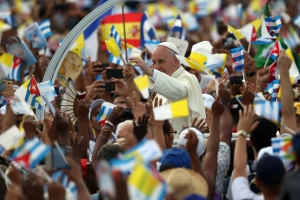People wave Cuban and Papal flags as Pope Francis passes by as he arrives to perform Mass on Sept. 20, 2015, in Revolution Square in Havana, Cuba. (Credit: Carl Court/Getty Images)