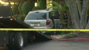 A minivan is hoisted onto a tow truck after a hit-and-run collision in Buena Park on Saturday, Sept. 12, 2015. (Credit: KTLA)