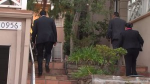 Investigators on Sept. 22, 2015, walk into a building where a woman was found dead after a fire near UCLA. (Credit: KTLA)