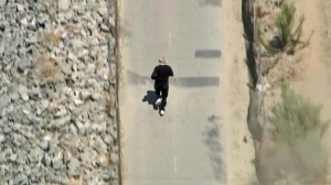 A man being pursued by authorities runs near the San Gabriel River on Sept. 2, 2015. (Credit: KTLA)