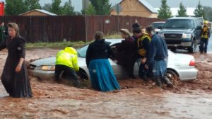 Fire and rescue workers pull a woman from a car in knee-deep flood water in the town of Hildale, Utah, along the Arizona border on Sept. 15, 2015. (Credit: Chris and Lydia Wyler via CNN Wire)
