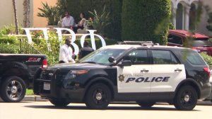 Investigators work outside an apartment complex where many Pi Beta Phi members live on Sept. 21, 2015, when a woman's body was found in a burning unit. (Credit: KTLA)
