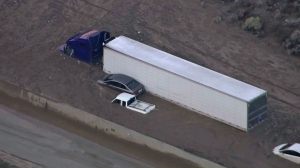 Several vehicles are seen trapped hood-deep in mud following a storm in the Mojave area. (Credit: KTLA)