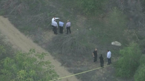Detectives were investigating in Debs Park, where two female bodies were discovered Oct. 28, 2015. One of the bodies has been blurred in this image. (Credit: KTLA)