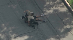 A deputy is seen punching a man at the end of pursuit in Pasadena on Oct. 15, 2015. (Credit: KTLA)