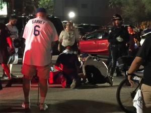 People tend to an injured person following a fight in the Dodger Stadium parking lot on Oct. 9, 2015. (Credit: Maria Cerecer)