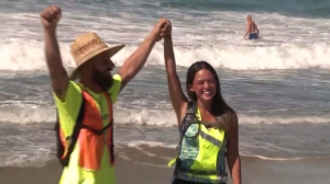 Keith Edwards and Reina Emerson rejoice after their more than 200 days walking across the U.S. ends in Huntington Beach on Oct. 2, 2015. (Credit: KTLA)