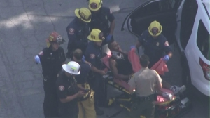 A man who had been taken into custody after a pursuit is seen being treated by firefighters in Pasadena on Oct. 15, 2015. (Credit: KTLA)