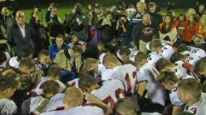 Players and fans join assistant coach Joe Kennedy in prayer on the football field after Bremerton High School's homecoming game. (Credit: KCPQ)