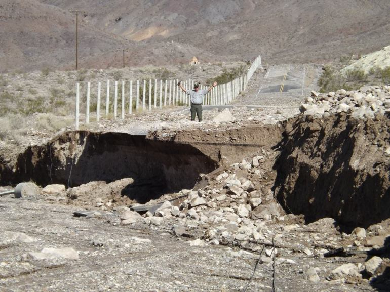 A park ranger stands on a road damaged in an Oct. 18, 2015, storm in Death Valley. (Credit: Death Valley National Park)