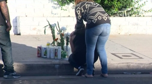 Eduardo Rebolledo's daughter is comforted Oct. 7, 2015, at the site where he was killed a day earlier. (Credit: KTLA)