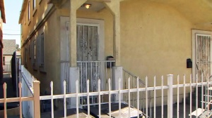 Multiple bullet holes are seen in the door to the home where a woman was shot on Oct. 19, 2015. (Credit: KTLA)