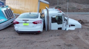 A car came to a rest on top of a partially buried big rig on State Route 58 after severe weather swept through the area on Oct. 16, 2015. (Credit: Kern County Sheriff's Office)