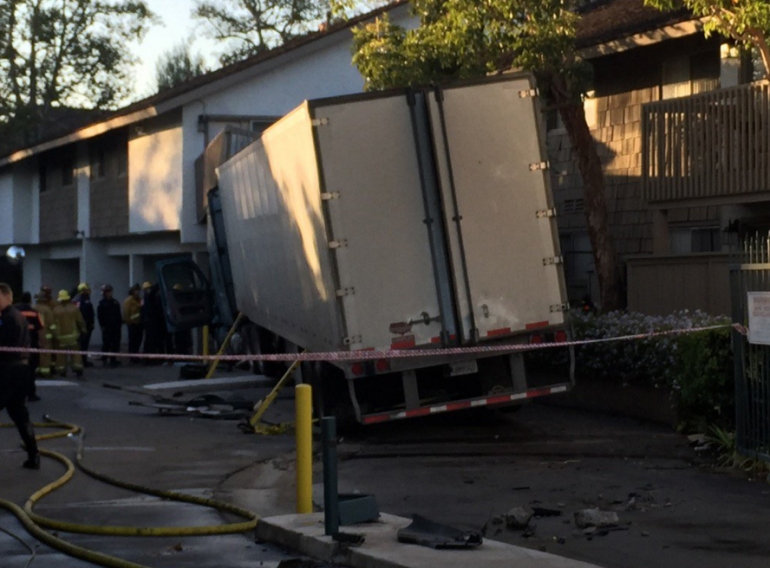 The driver of a big rig was injured after the truck crashed into an apartment building in Orange on Nov. 9, 2015. (Credit: Chip Yost/KTLA)