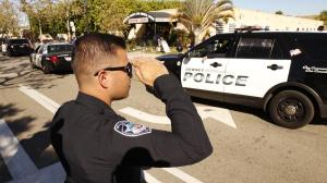 Bell Gardens police Officer Steven Perez salutes as the coroner's van departs from the scene where Downey police Officer Ricardo Galvez was found shot to death in the driver's seat of his vehicle in a Downey parking lot on Nov. 19, 2015. (Credit: Al Seib / Los Angeles Times)