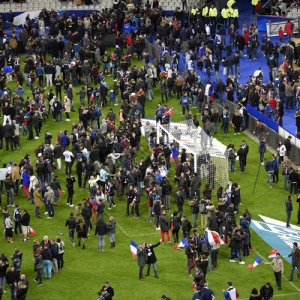 Football fans gather in the field as they wait for security clearance to leave the Stade de France in Saint-Denis, north of Paris, after the friendly football match France vs Germany on November 13, 2015 following shootings and explosions near the stadium and in the French capital. (Credit: FRANCK FIFE/AFP/Getty Images)