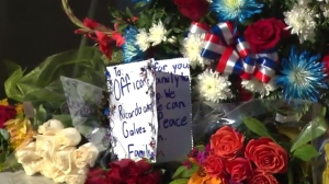 Flowers and a card are seen Nov. 19, 2015, at Downey police station in honor of Officer Ricardo Galvez, who was killed the previous night. (Credit: KTLA)
