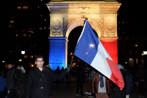 A man waves a flag as the Washington Square Park arch is lit with the French national colors in solidarity with the citizens of France on Saturday, Nov. 14, 2015, in New York, a day after the Paris terrorist attacks. (Credit: Jewel Samad/AFP/Getty Images)