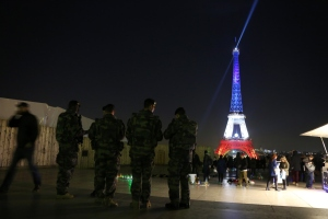 French soldiers are seen patrolling on Nov. 23, 2015, in front of the Eiffel Tower, illuminated in the colors of the French flag as a tribute to the victims of the Nov. 13 terrorist attacks. (Credit: Ludovic Marin/AFP/Getty Images)