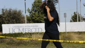 A UC Merced student walks past police tape to leave campus after stabbings on Nov. 4, 2015. (Credit: Michael Robinson Chávez / Los Angeles Times)