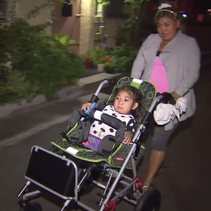 Four-year-old Miracle tries out a new stroller donated by a local businessman after the girl's custom wheelchair was stolen. (Credit: KTLA)