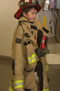 Nathaniel Stocks, 5, is seen wearing a firefighter's jacket after being honored by the San Bernardino County Fire Department. (Credit: KTLA)