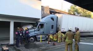 Firefighter work to stabilize a big rig that crashed into an apartment building in Garden Grove on Nov. 9, 2015. (Credit: KTLA)