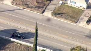 At least one person appeared to be dead in the street near a shot-out SUV in San Bernardino on Dec. 2, 2015, following a mass shooting. (Credit: KTLA)