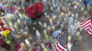 Candles and American flags were included in a growing memorial dedicated to the victims of a deadly shooting in San Bernardino on Dec. 2, 2015. (Credit: KTLA)