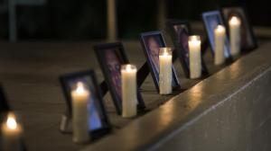 Framed photographs of the 14 slain in the San Bernardino shooting rampage are lit by candlelight on a stage during a vigil in Colton on Dec. 10, 2015. (Credit: Gina Ferazzi / Los Angeles Times)