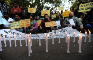 Indian protestors sit behind lighted candles during a protest in New Delhi on Dec. 29, 2012, after the death of a gang rape victim. (Credit: SAJJAD HUSSAIN/AFP/Getty Images)