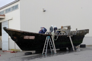 Coast guard officials on Nov. 24, 2015, investigate a wooden boat at the Fukui port in Sakai city in Fukui prefecture, western Japan, after the ship was found drifting off the coast of Fukui. (Credit: JIJI PRESS/AFP/Getty Images)